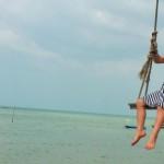 World-for-kids.com Kind auf Schaukel über dem Meer